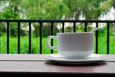 Coffee cups, saucers and white coffee spoons on the balcony have a green tree background. Stockfoto