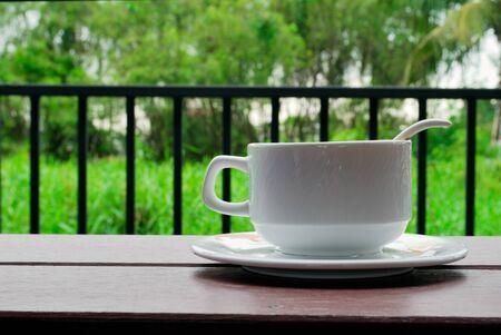 Tazas de café, platillos y cucharas de café con leche en el balcón tienen un fondo de árbol verde. Foto de archivo