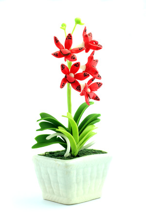 Red fake flowers in the vase on white background photo