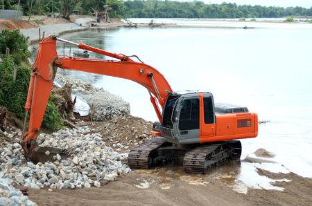dumper: Excavator machine loading dumper truck at river in bantak,Thailand
