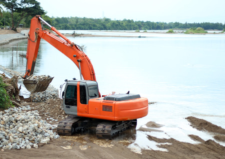 construction vehicle: Excavator machine loading dumper truck at river in bantak,Thailand