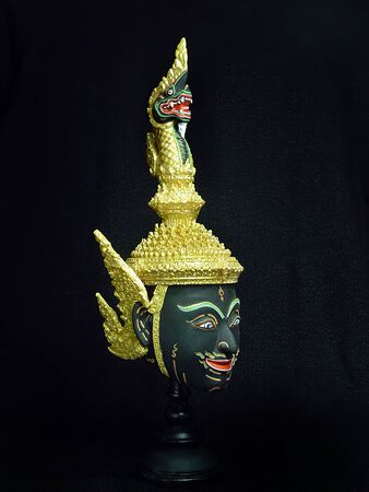 A model of thai actor's Khon mask on black background.(Thai traditional dance) Use in khon thai classical style of ramayana story. Serpent king or nakhrach mask in native thai style Foto de archivo