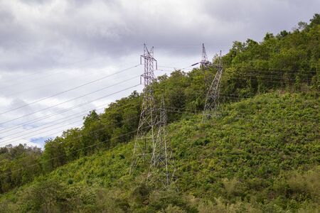 Image of high voltage electricity pylon and transmission power line with sky and mountain background.
