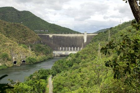 Image of front view of Bhumibol dam in Tak. Hydro Power Electric Dam and is the first multipurpose dam in thailand and is water storage for agriculture and electricity.. The curved concrete dam.
