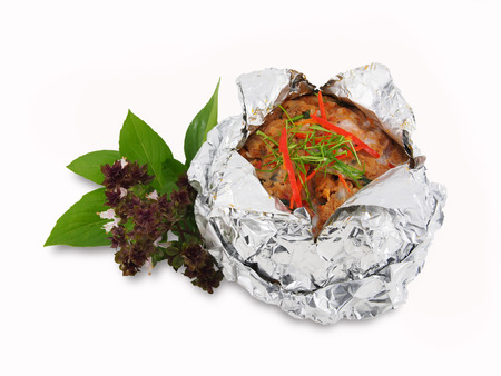 Steamed seafood curry paste cake in foil on white photo