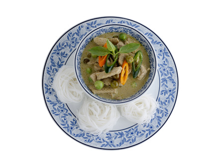 Thai green curry pork and rice noodles served on dish with white background photo