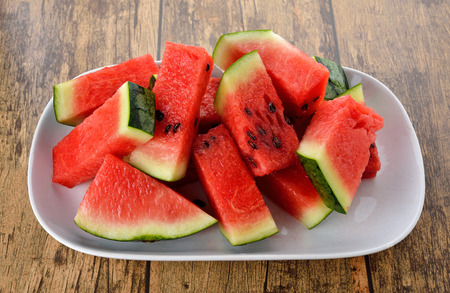 sliced watermelon: sliced watermelon on plate with wood table background Stock Photo