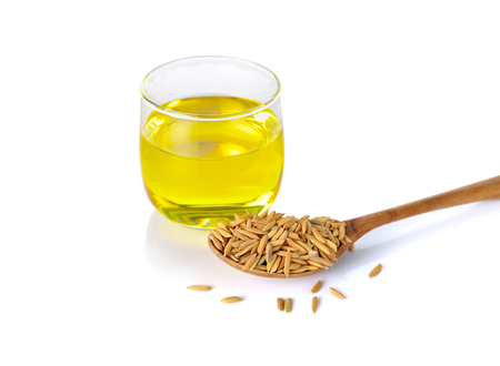 rice bran oil in glass and paddy on wooden spoon with white background