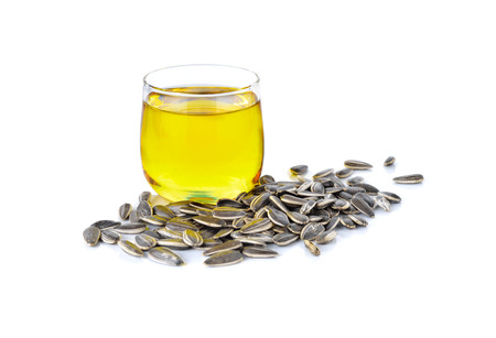 sunflower oil in glass and sunflower seeds on white background