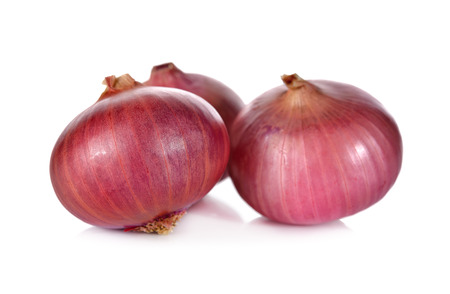 unpeeled: unpeeled whole red onion, shallots on white background