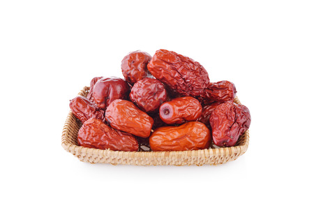 dried Chinese Jujube fruit in bamboo basket and on white background Stock Photo