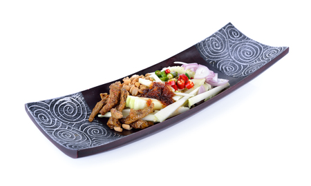green mango spicy salad with crispy fish on wooden plate
