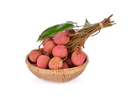 whole lychee fruit with stem and leaves in basket on white background Stock Photo