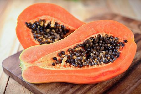 Half coupé ripe papaye avec des graines sur planche de bois Banque d'images - 80204295