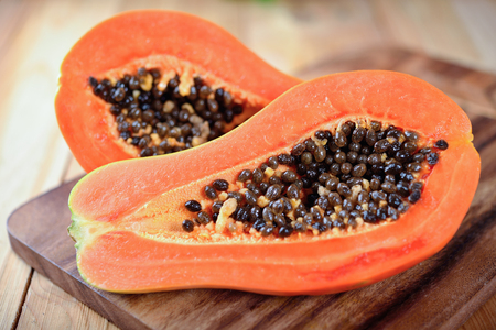 half cut ripe papaya with seeds on wooden board