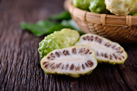 whole and half cut fresh noni fruit with leaf on wooden background