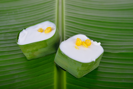 authentic Thai dessert, Creamy Coconut Tapioca and Corn Pudding on banana leaf background