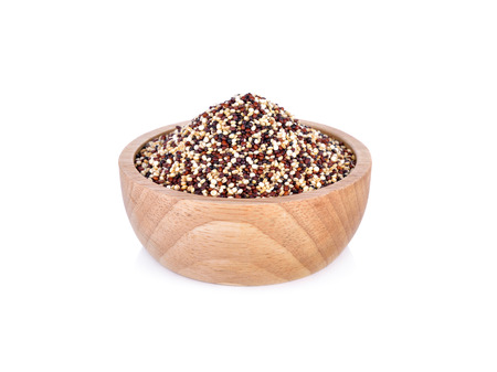 dry tricolor quinoa in wooden bowl on white background