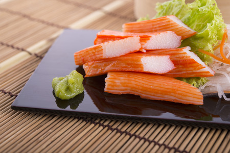 crab sticks with wasabi on black plate and on bamboo mat
