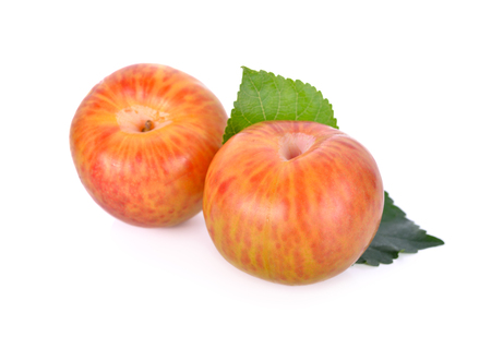 whole fresh pluot on a white background