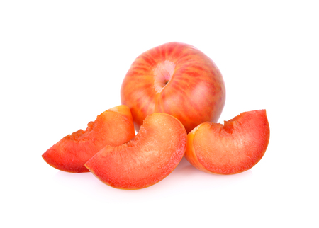 whole and sliced fresh pluot on a white background Imagens