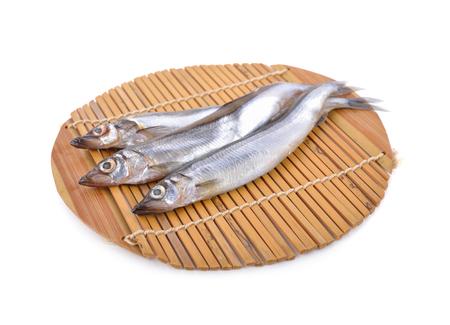 whole round fresh shishamo fish on bamboo mat with white background