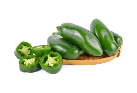 whole and portion cut fresh Jalapeno or Mexican Chili on white background