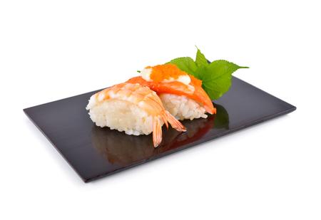 Sushi nigiri and sashimi served on flat black plate with white background
