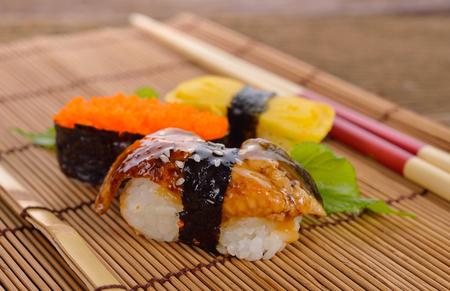 Sushi nigiri and sashimi served on bamboo mat with chopsticks on wooden background