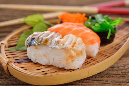 Sushi Set nigiri and sashimi served in bamboo plate on wooden background Stock Photo