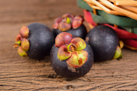 whole fresh Mangosteen on wooden table Stock Photo