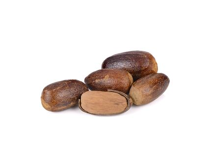whole dried nutmeg with shell on white background Stock Photo