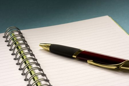 working week: Blank green spiral notepad with burgundy pen