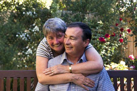 Loving elderly couple hugging on a park bench Stock Photo - 2562252