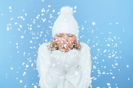 Blonde girl blows snowflakes off fluffy mittens towards the camera on an isolated blue background. The girl is dressed in a warm fluffy white sweater knitted hat with a bubo. Photographed close-up.