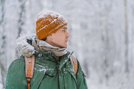 A man in clothes covered with snow looks forward to the snow-covered forest. The man is dressed in a green warm jacket and a red hat. Search in the winter forest. Christmas mood.