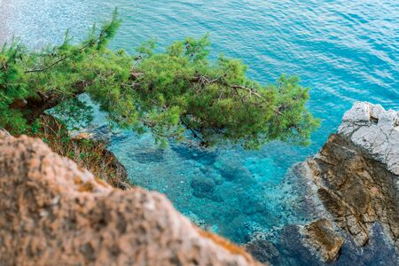 Beautiful view from the cliff to the clear azure sea. Rocks and clear waters of the Adriatic sea