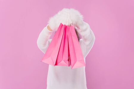 Girl holding pink paper bags over isolated pink background. A girl holding packets at the head covering his face. A girl in a sweater and fluffy mittens.