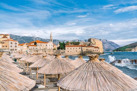 The old town of Budva. The Beach Of Budva. Umbrellas on the beach in the foreground. Clear Sunny day, blue sky over the city and mountains. Sea waves break on the pier. 版權商用圖片