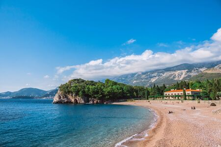 Beautiful landscape of Adriatic sea beach with mountains in the background. Blue transparent sea, blue sky, Sunny weather and white clouds over the mountains. Villa with red roof 版權商用圖片