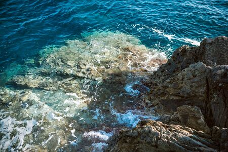 Rocky coast of the Adriatic sea. Rocks and clear sea Water. Waves break on the shore. Bright sunny day.