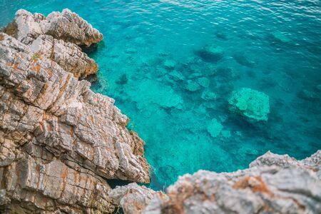 Beautiful sea coast of the Adriatic sea. Azure water and brown rocks. Top view Banco de Imagens