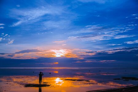 Silhouette of a man photographing the dawn on a smartphone. A man photographs the seascape at dawn. Sunrise over Sanur beach Bali Indonesia