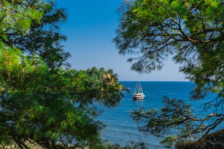A tourist ship stands near the coast in the Mediterranean sea Turkey.The most popular tourist attraction is a boat tour along the Mediterranean coast. Tourism in Turkey.