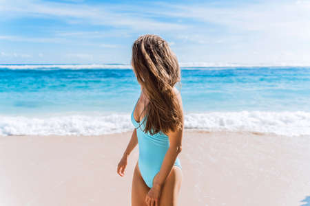 A beautiful girl in a blue swimsuit stands against the blue ocean and looks towards the water.