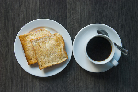 Cup of coffee and slices of toast on wooden table from top photo
