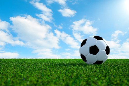 Soccer ball on green field with bright sky background photo