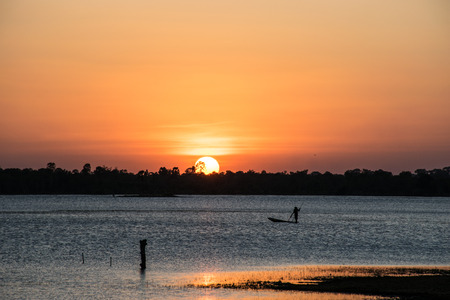 emanate: Fisherman boating in the river, sunset background Stock Photo