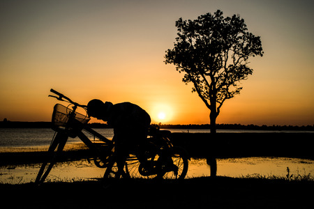 avocation: Boy sitting on the bike in the evening river, sunset background