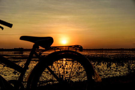 Bicycle in the evening, the sun above it, with sunset background